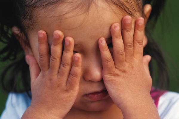 child covering face