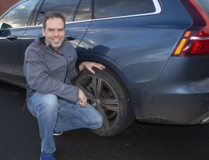 Man checking car tyres to make sure they are safe for winter driving conditions.