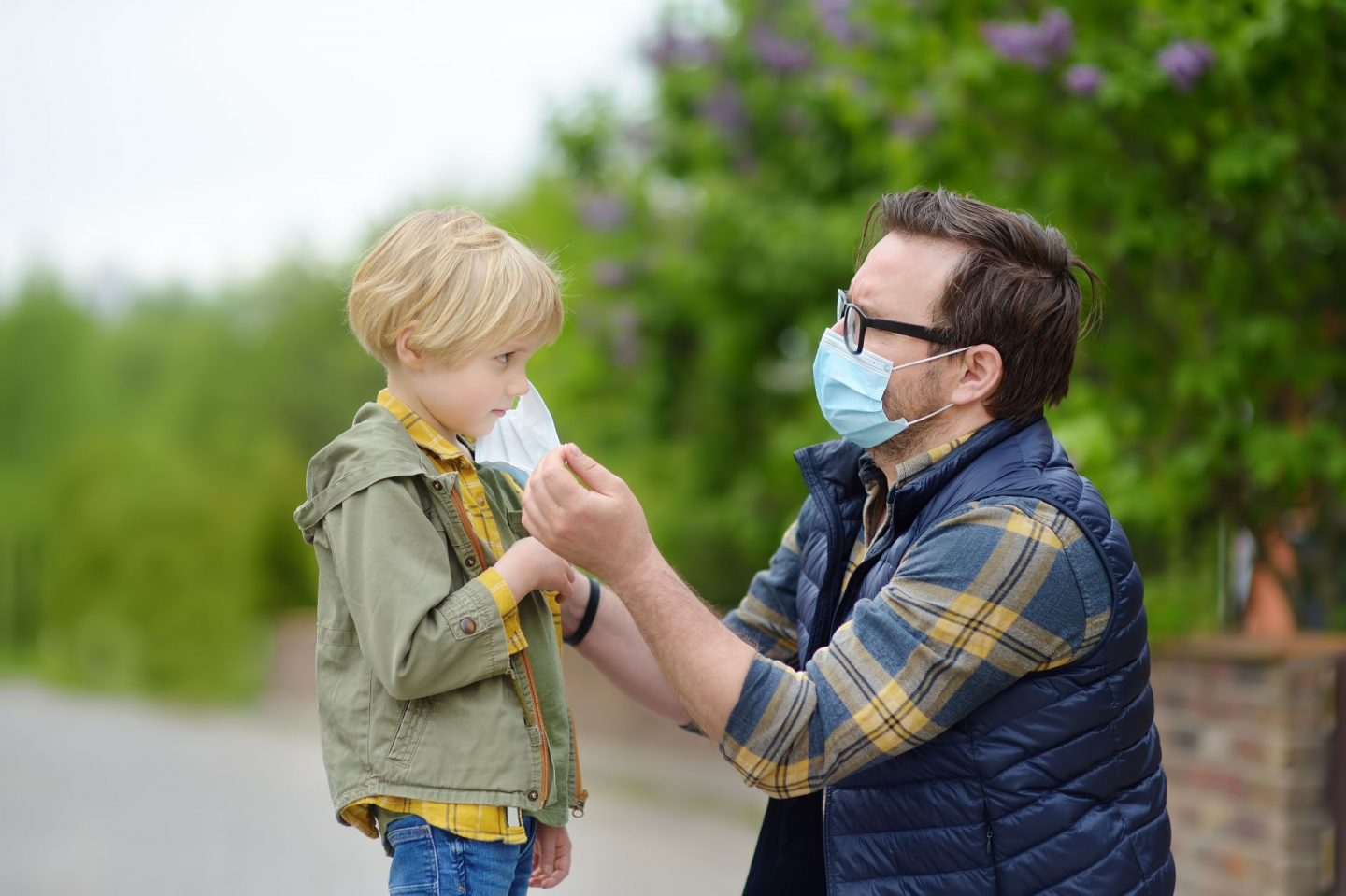 The COVID-19 generation are not snowflakes. Picture of man putting face mask on a child.