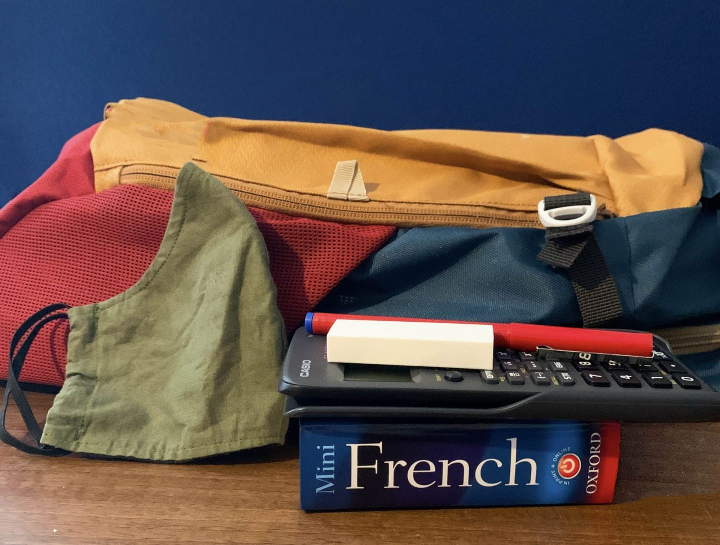Back to school. School bag with face mask, book, calculator and pen.