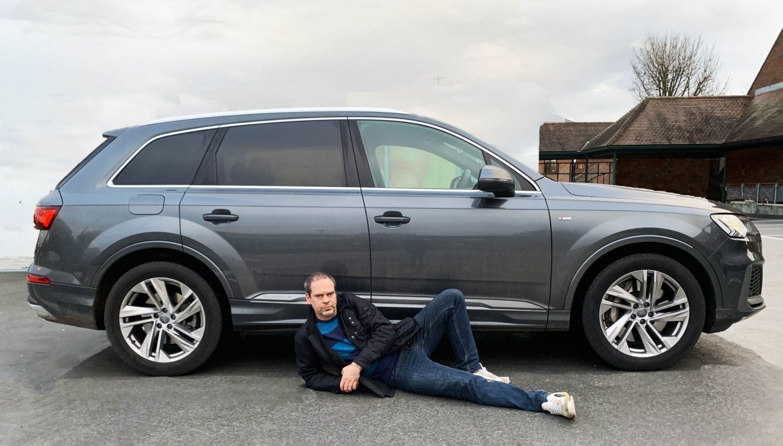 John Adams of Dadbloguk lying down next to an Audi hybrid Q7.