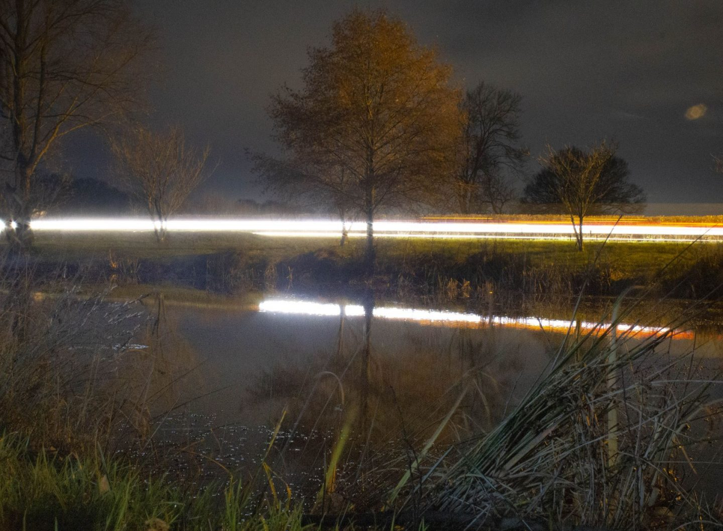 Experimental long-exposure image of car reflected in a pond.