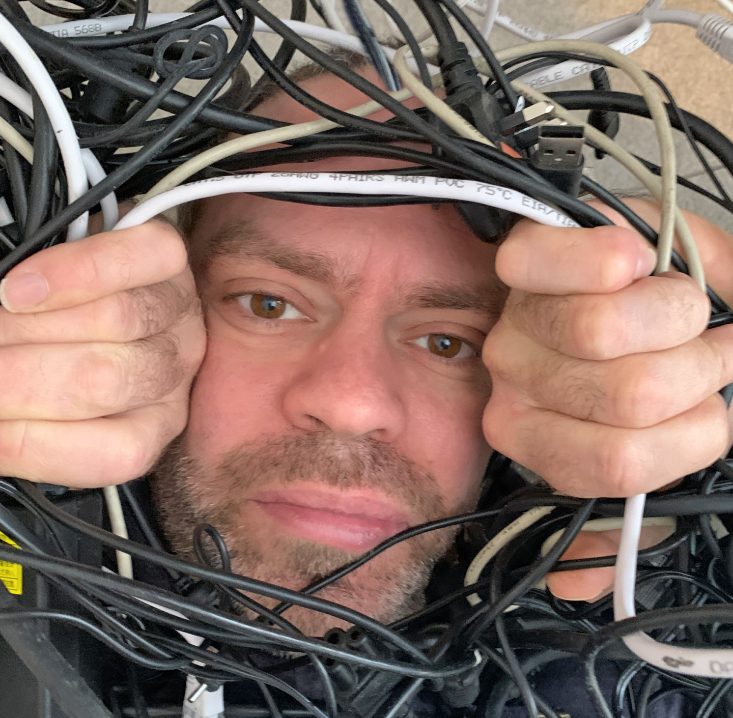 Man surrounded by wires while helping his children with home learning.