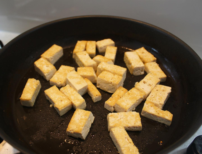 Tofu browning in a frying pan.