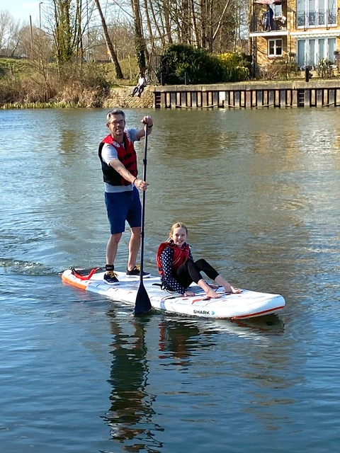 Man and child using SUP on a river