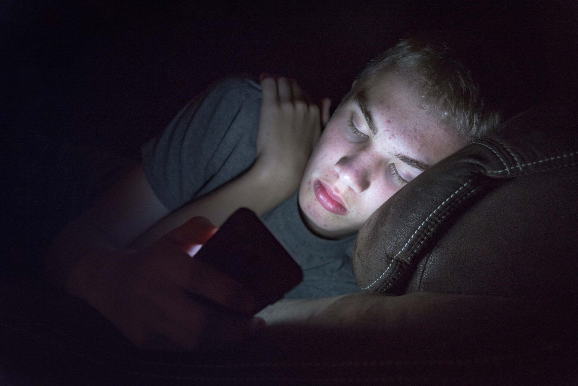 Teenager setting screen time rules on his phone