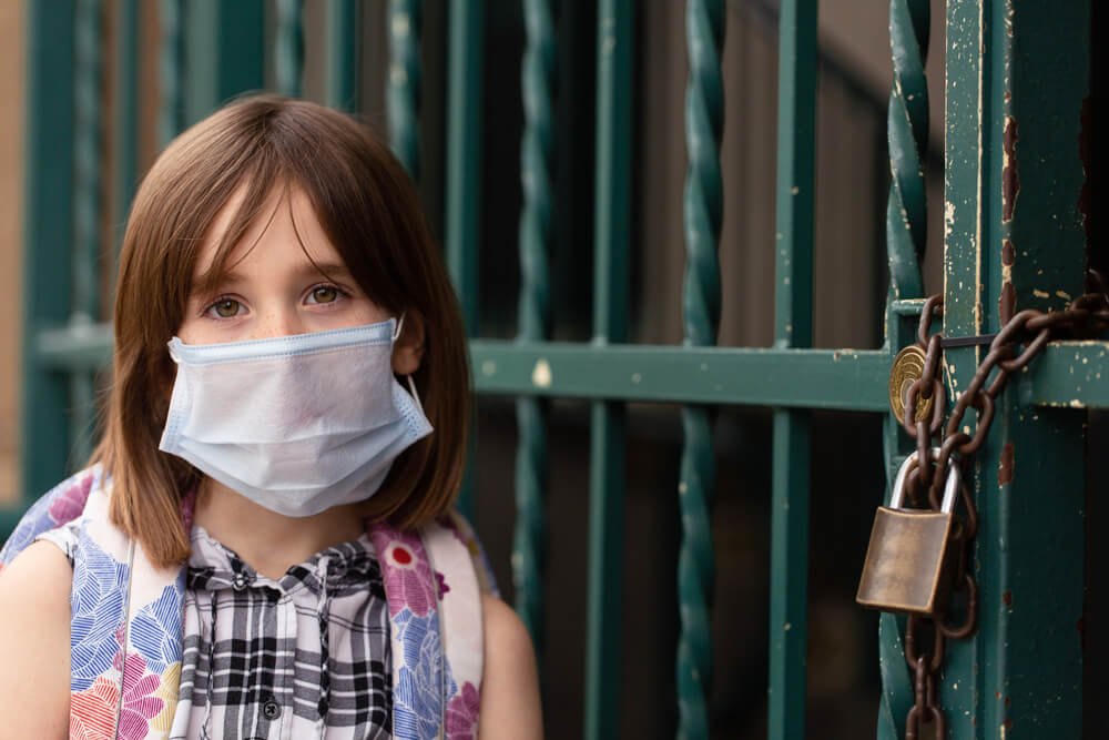 academic year comes to an end. Girl in face mask at school gates
