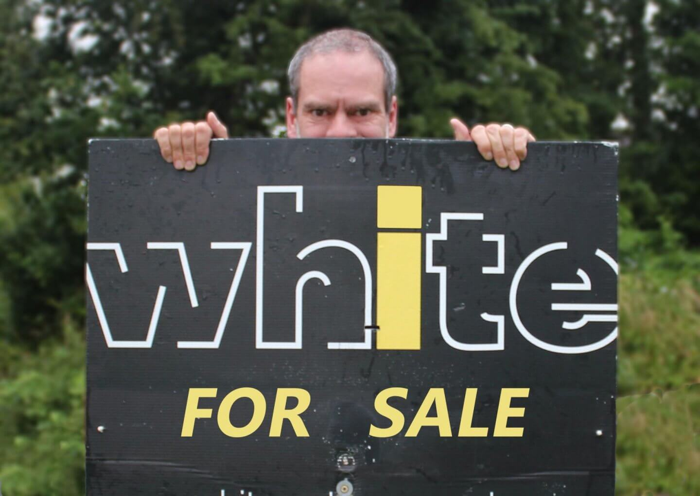 Selling up and moving on. Man with realty for sale sign.