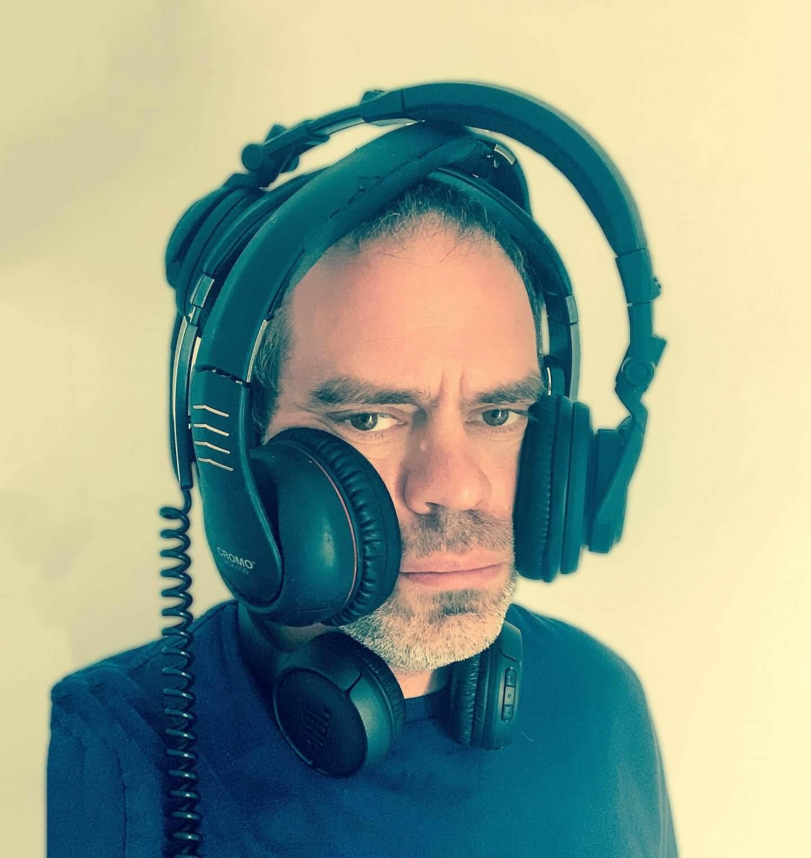 Educating children about music. Man wearing multiple headphones